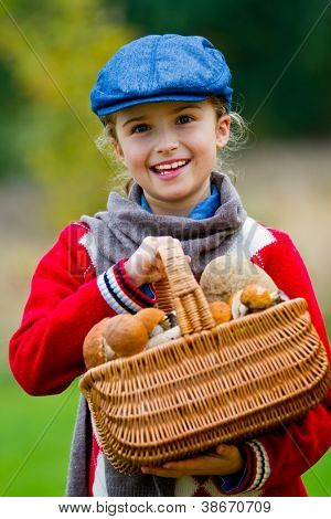Mushrooms picking, season for mushrooms - lovely girl with basket of picked fresh edible mushrooms