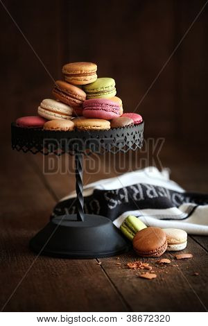 Metal cake stand with macaroons on dark wood background