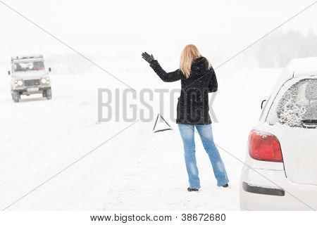 Mulher pedindo carona tendo problemas com assistência de Inverno de neve de carro quebrado