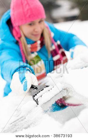 Woman brushing snow from car windscreen winter work scraper wiping