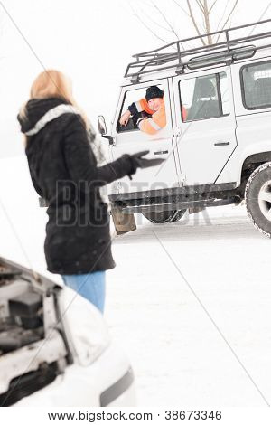 Woman having trouble with car snow assistance winter talking man