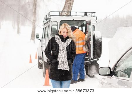 Mechanic helping woman with broken car snow assistance road winter