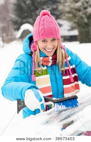 Woman wiping car windshield using brush snow winter happy work