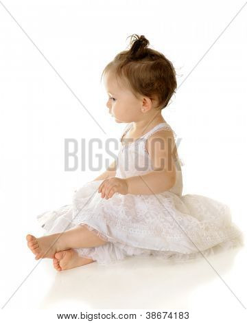 High key profile of an adorable baby girl sitting pretty in her petticoat.  On a white background.