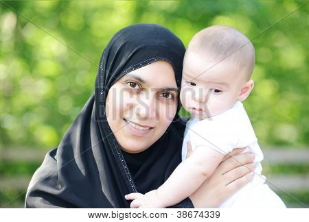 Muslim mother with her baby in green nature