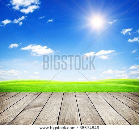 Green field under blue sky. Wood floor