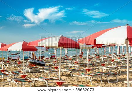 Red And White Umbrellas And Sunlongers On The Sandy Beach