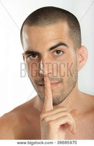 Young man putting a finger on his lips