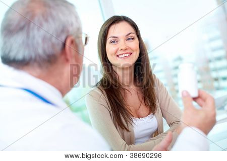 Portrait of pretty patient listening to mature practitioner in hospital