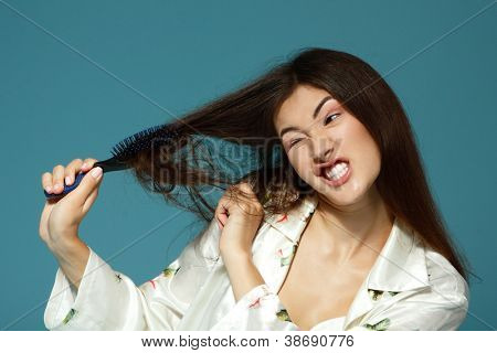 Funny teen girl bombing her problem hair in the morning. Over blue background.