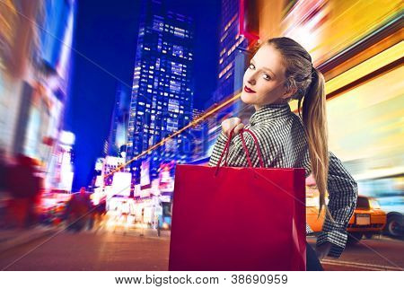Beautiful blonde girl holding a red shopping bag in New York