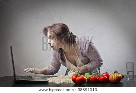 Woman is checking a recipe on a laptop computer while she is cooking
