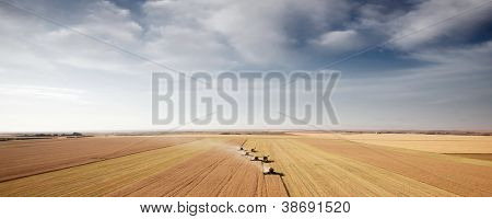Panoramic landscape with four combines in a field on the open prairie
