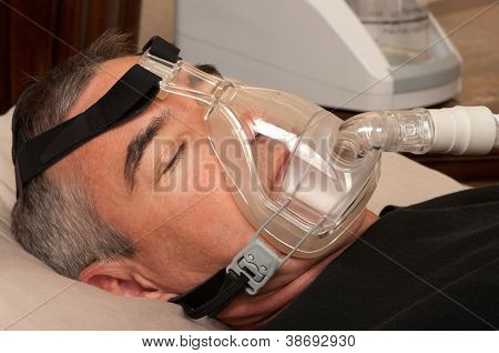 Man with sleeping apnea and CPAP machine