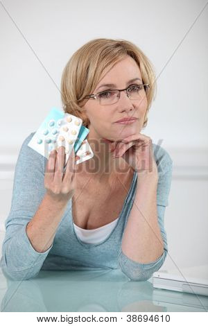 Blond woman holding various prescription drugs