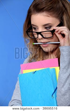 Geeky student holding folders