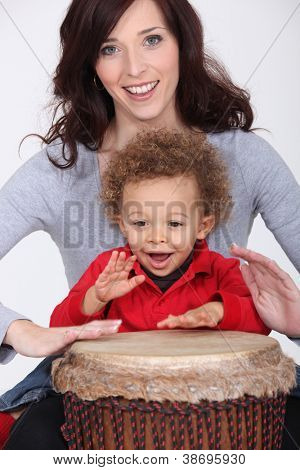 Little boy and mother playing bongo drum