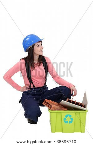 Young tradeswoman squatting beside a recycling bin