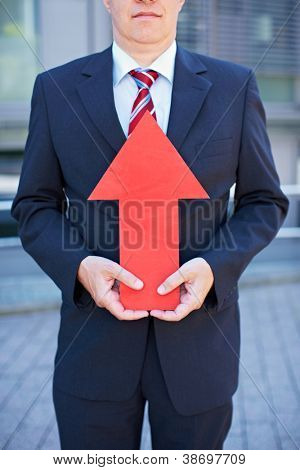 Business man with red arrow pointing up towards his face