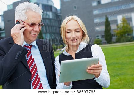 Two business people with smartphone and tablet PC outdoors