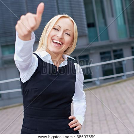 Cheering happy business woman holding her thumbs up