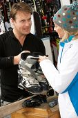 image of ski boots  - Sales Assistant Helping Advising Female Customer On Ski Boots In Hire Shop - JPG