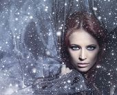 stock photo of redhead  - Fashion shoot of young attractive woman in blowing silk over the snowy background - JPG