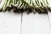stock photo of bundle  - Close up of fresh green asparagus on wooden table - JPG