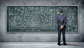 foto of business class  - Business person standing against the blackboard with a lot of data written on it - JPG