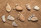 picture of wander  - trace bare feet walking made of pebble stones on the beach sand background - JPG