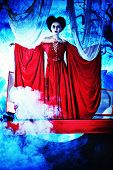 Bloodthirsty female vampire rises from the coffin on the night cemetery. poster