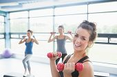 picture of step aerobics  - Smiling woman lifting weights while women doing aerobics in gym - JPG