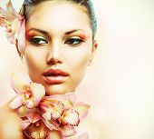 Beautiful Girl With Orchid Flowers.Beauty Woman Face.Vogue Styled Fashion Portrait. Professional Mak