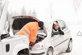 Man repairing woman's car snow assistance winter broken tools mechanic