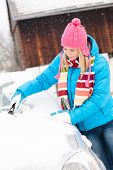stock photo of ice-scraper  - Woman cleaning snow car hood with scraper winter wiping young - JPG