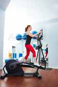 picture of elliptical  - Aerobics cardio training woman on elliptic crosstrainer bicycle at gym - JPG
