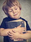 picture of hardcover book  - Little boy hugging an old book - JPG