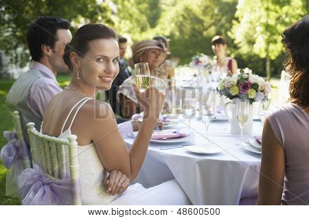 Portrait of beautiful bride holding champagne flute while sitting with guests at wedding table