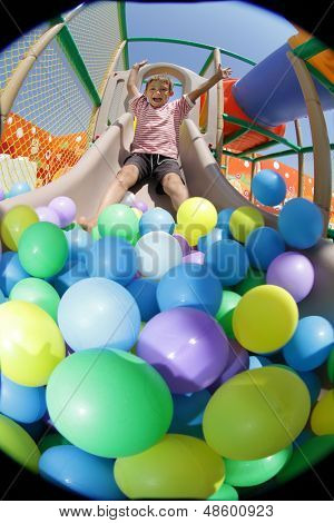boy playing in playground colourful ball pool