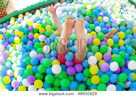 Baby girl playing in playground colourful ball pool