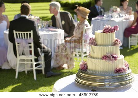 Closeup of weeding cake with guests at tables in background