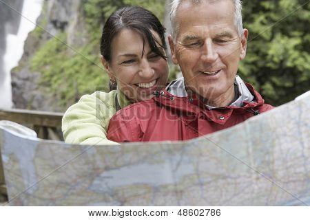 Maduro hombre y mujer leyendo el mapa con cascada en el fondo