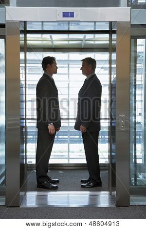 Side view of businessmen standing face to face in elevator