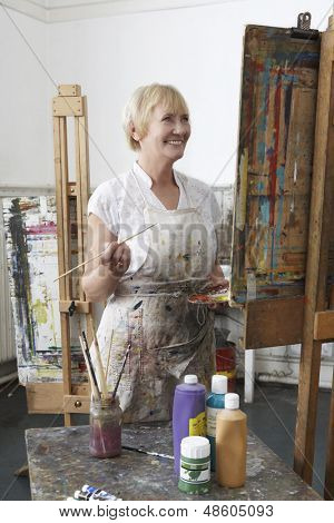 Smiling mature female artist painting at easel in art studio