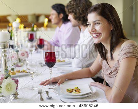 Alegre joven sentado con amigos en la cena