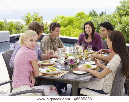 Retrato de una mujer feliz con multiétnicas amigos disfrutando de la comida en el patio