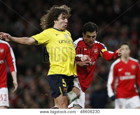 LONDON, ENGLAND. 31/03/2010. Barcelona player Carles Puyol fouls Arsenal player Cesc Fa?bregas during the  UEFA Champions League quarter-final between Arsenal and Barcelona at the Emirates Stadium