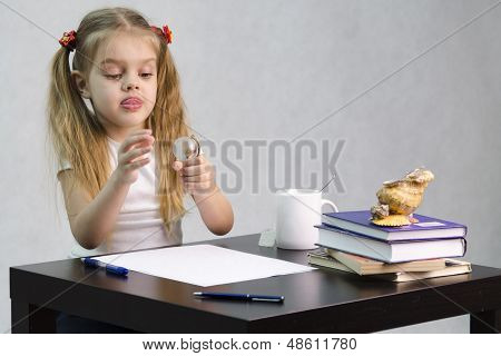 The girl thoughtfully and effortlessly turns the glass globe, sitting at the table in the image