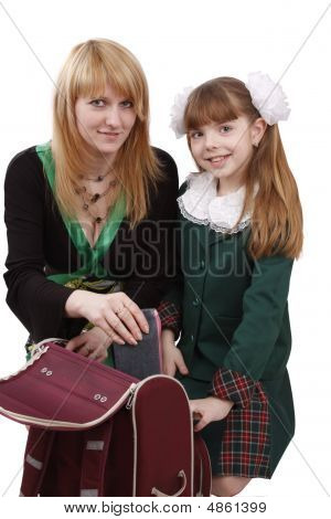 Mother Is Packing Up Backpack With Daughter.