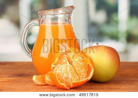 Full jug of multivitamin juice on bright background